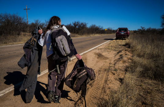 Alex Webb USA. Arizona. 2019. Trip to desert with Tucson Samaritans to look for migrants, pick up migrants' clothes and trash, and leave water for migrants. Ila Abernathy with discarded migrant clothes.